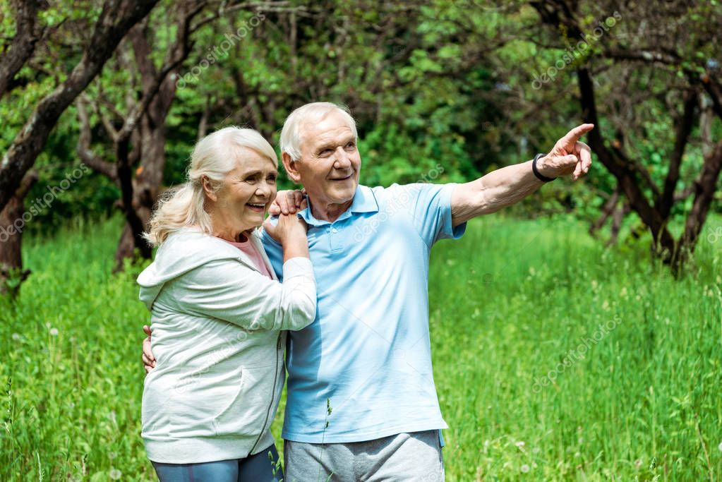cheerful retired man pointing with finger near happy wife with grey hair