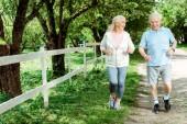veselý muž v důchodu s běžícím poblíž starší ženy v parku
