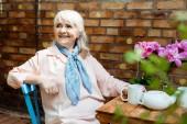 Veselá žena se usmívá, když sedí u šálků a čajové konvice