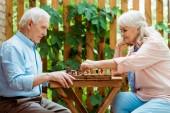 donna in pensione con i capelli grigi giocare a scacchi con il marito anziano
