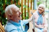 selektivní zaměření šťastného manžela v důchodu hrající akustickou kytaru u starší ženy