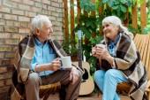 šťastný starší muž, který se dívá na veselou ženu, držící šálek čaje