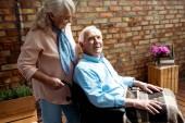 Veselá starší žena stojící nedaleko invalidního manžela v invalidním křesle