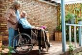 selektivní zaměření veselého staršího muže stojícího poblíž invalidního manžela na vozíku