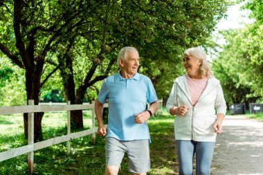 happy retired woman running near senior husband in park