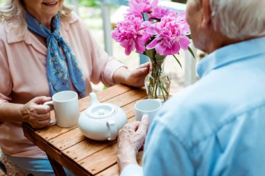 cropped view of senior couple holding cups while sitting near teapot