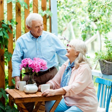 happy senior man standing and looking at cheerful wife near cups