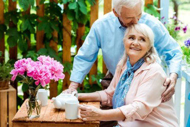 happy senior man kissing cheerful wife sitting near cups