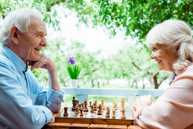 cheerful retired woman with grey hair playing chess with senior husband