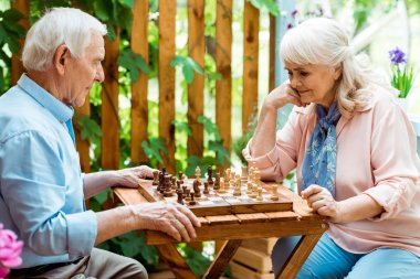 retired woman with grey hair playing chess with senior man