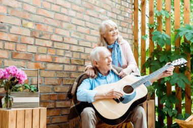 low angle view of retired husband playing acoustic guitar near happy wife