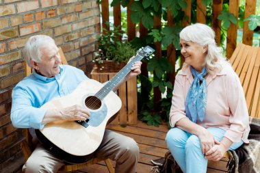 Happy retired woman looking at husband playing acoustic guitar stock vector