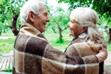Senior husband hugging happy retired wife in plaid blanket stock vector