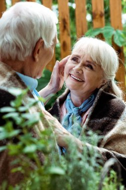 selective focus of happy woman with grey hair looking at retired husband
