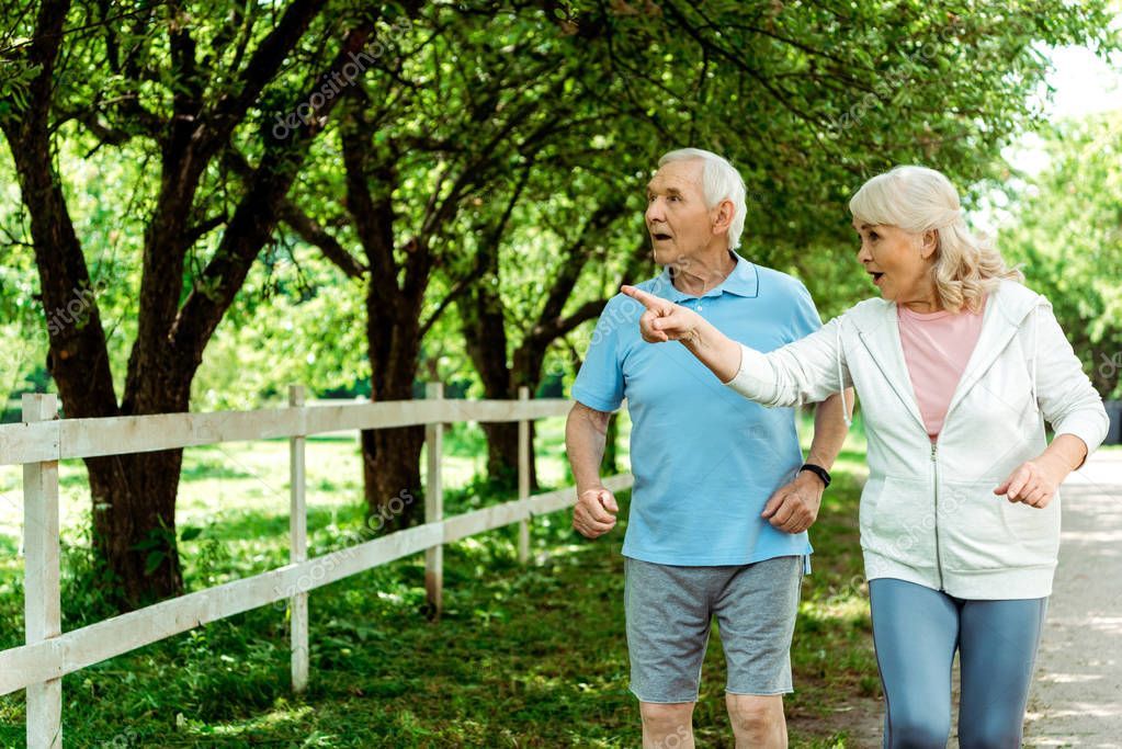 retired woman with grey hair pointing with finger near surprised husband