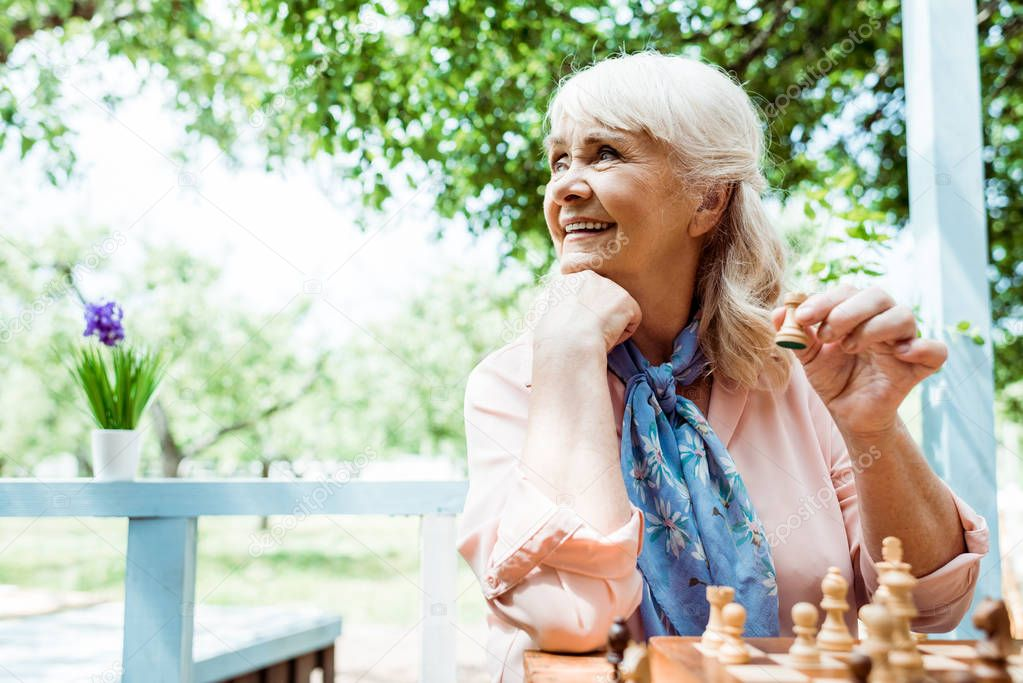 selective focus of cheerful retired woman holding wooden figure while playing chess