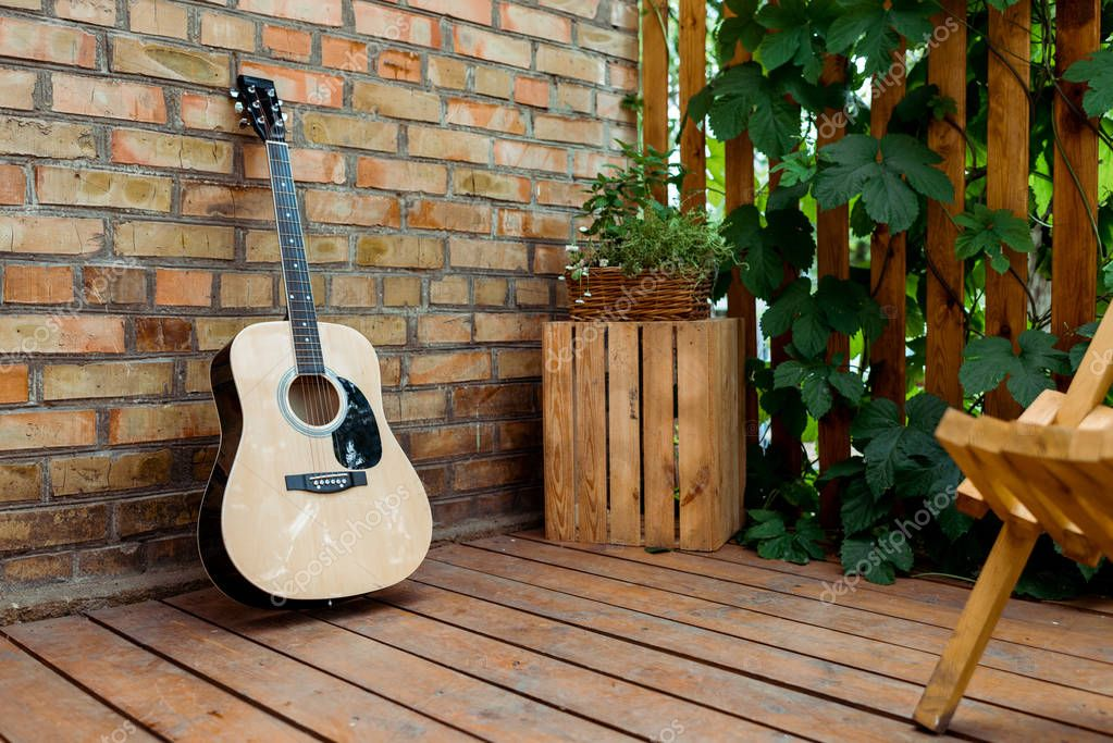 selective focus of acoustic guitar near brick wall and wooden fence with green leaves