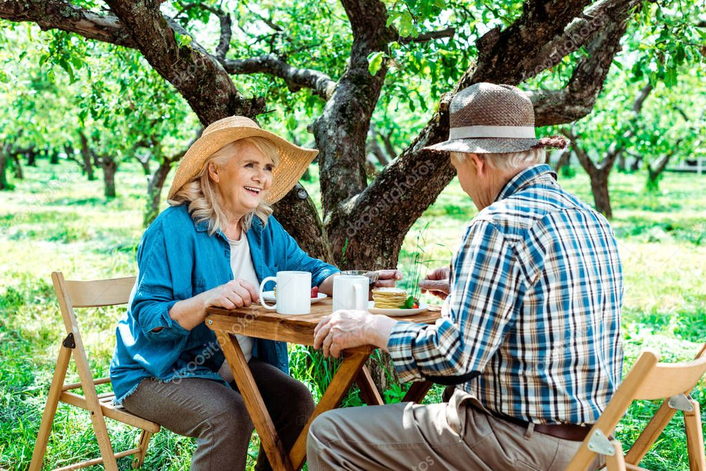 cheerful senior woman in straw hat looking at husband near tree