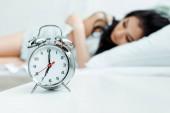 selective focus of retro alarm clock near sleeping girl