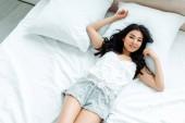 stropní pohled na šťastnou asijskou dívku ležící doma na posteli