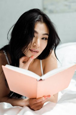 Selective focus of pretty thai woman holding book and looking at camera stock vector