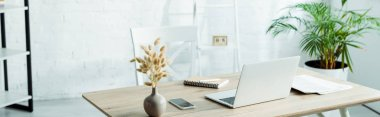 panoramic shot of laptop and smartphone on wooden table in modern office