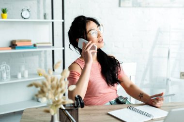 Selective focus of attractive asian businesswoman in glasses talking on smartphone in office stock vector
