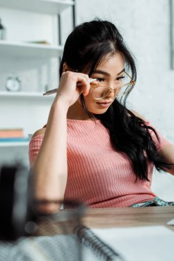 Selective focus of asian woman touching glasses in office stock vector
