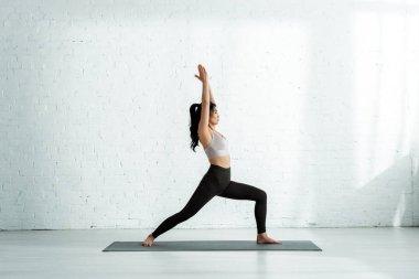 beautiful brunette thai woman doing exercise on yoga mat