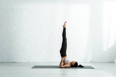 beautiful thai woman doing exercise on yoga mat near  brick wall