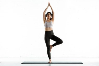 attractive thai woman standing on yoga mat and doing exercise on white