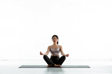 Calm asian woman sitting on yoga mat and doing exercise on white stock vector