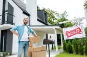 handsome man standing with hand on hip and holding box near house and board with sold letters