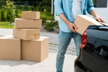 Cropped view of man standing near car while putting box stock vector