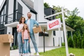 šťastný muž držící skříňku a stát se ženou a dcerou poblíž domu a lepenky s prodávanými dopisy