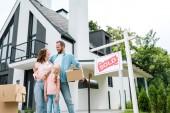 Szakállas férfi Holding Box és állva a felesége és lánya közelében ház és a fedélzeten eladott betűk
