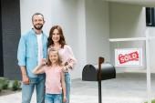 šťastný muž stojící se ženou a dcerou poblíž domu a lepenky s prodávanými dopisy