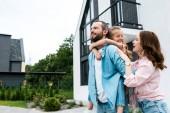 šťastný muž prasečí dcera v blízkosti veselé ženy a domu