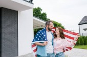 Fényképek happy bearded man standing with attractive woman and holding american flag