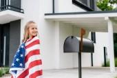 Fényképek happy kid standing with american flag near mail box