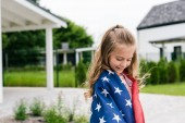 Fényképek happy child standing with american flag near house