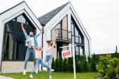 šťastný kluk držící medvídka a skáče s rodiči blízko domu