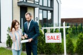 Photo attractive woman looking at clipboard while standing near broker and house