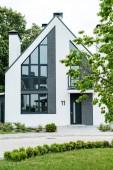 selektiver Fokus von grünem Gras in der Nähe des neuen modernen und luxuriösen Hauses