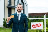 glücklicher bärtiger Mann im Anzug mit Kreditkarte in der Nähe seines Hauses