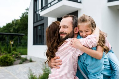 cheerful bearded man and happy kid hugging with woman near house