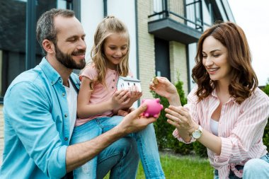 happy woman putting golden coin in piggy bank near husband and daughter