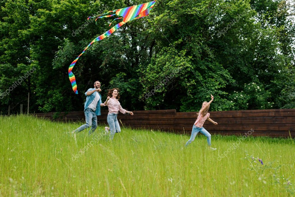 happy kid running with colorful kite on green grass near parents