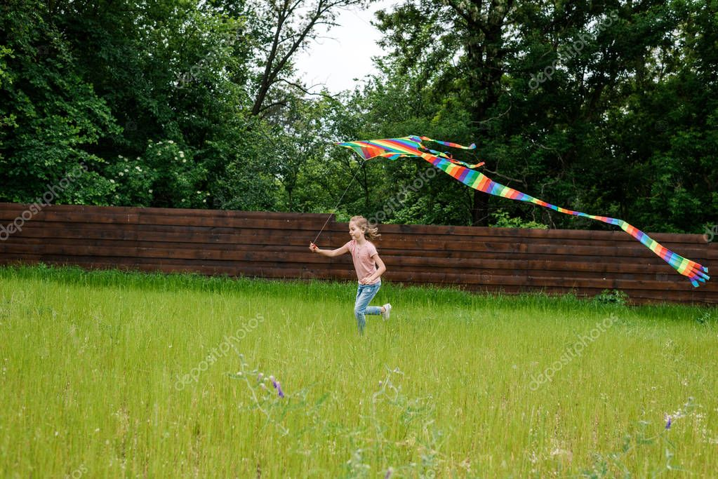 happy kid running with colorful kite on green grass outside