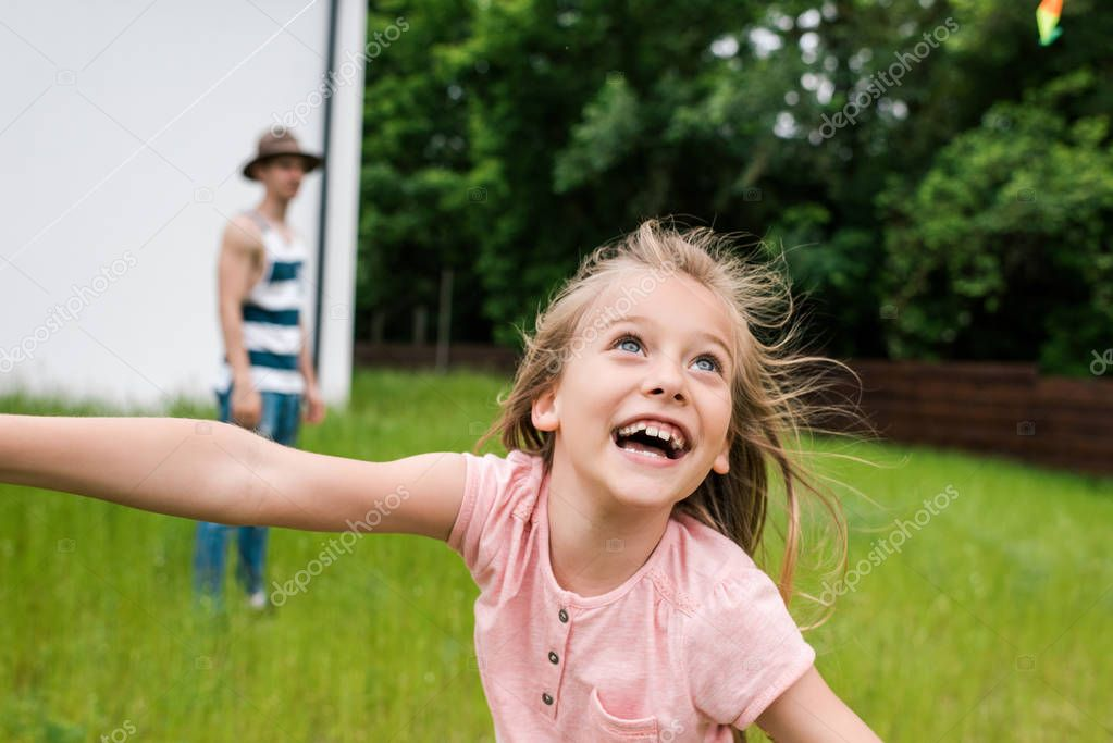 selective focus of happy kid smiling near father outside